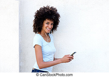 Smiling woman holding mobile phone and listening to music