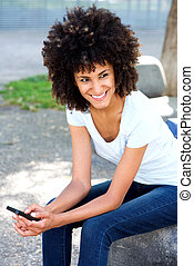 Smiling woman holding mobile phone in urban park