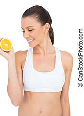 Smiling woman holding orange slice