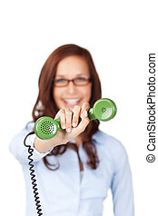 Smiling woman holding out a telephone receiver