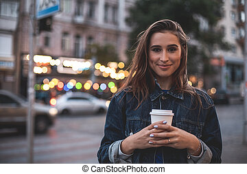Smiling woman holding plastic cup outside