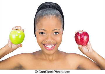 Smiling woman holding red and green apple looking at camera