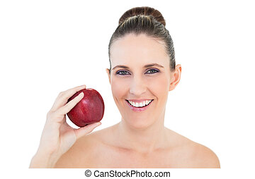 Smiling woman holding red apple and looking at camera