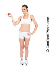 Smiling woman holding red apple looking at camera