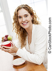 Smiling woman holding red coffee cup