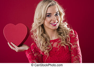 Smiling woman holding red heartshape box