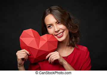 Smiling woman holding red polygonal heart shape - Closeup of...