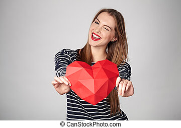 Smiling woman holding red polygonal paper heart shape -...