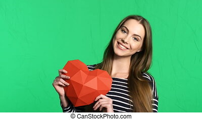 Portrait of beautiful smiling woman with red lips holding red polygonal paper heart shape