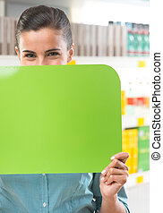 Smiling woman holding sign at supermarket