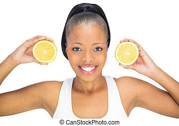 Smiling woman holding slices of orange