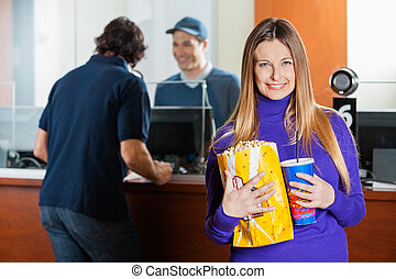 Smiling Woman Holding Snacks While Man Buying Movie Tickets