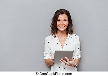 Smiling woman holding tablet computer in hands