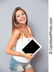 Smiling woman holding tablet computer - Portrait of a young ...