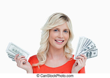 Smiling woman holding two fans of dollar notes in her hands