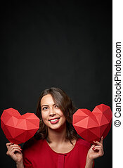 Smiling woman holding two polygonal heart shape - Smiling...