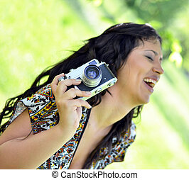 Smiling woman holding vintage camera