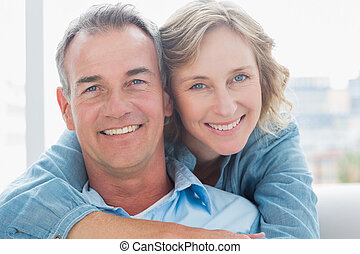Smiling woman hugging her husband on the couch from behind