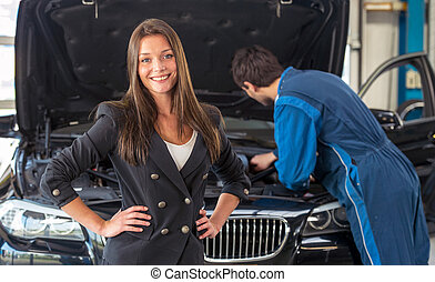 Smiling woman in a car servicing garage