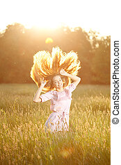 Smiling woman in a field at sunset with flying hair