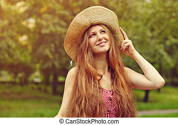 smiling woman in a hat in summer park