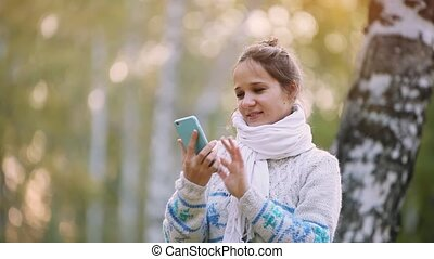 Smiling woman in a knitted sweater and scarf making selfie with mobile phone in park during the autumn. 1920x1080
