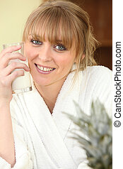Smiling woman in bathrobe with glass of milk
