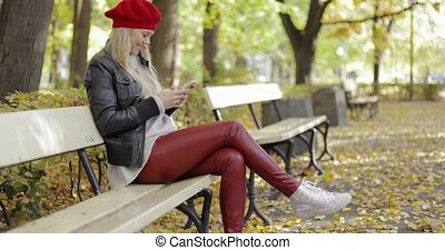 Smiling woman in beret using smartphone