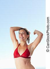 Smiling woman in bikini stretching