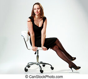 Smiling woman in black dress sitting on the office chair over gray background