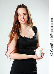Smiling woman in black dress standing and holding cup with coffe over gray background