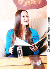 Smiling woman in blue at cafe table