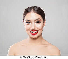 Smiling woman in braces on white background