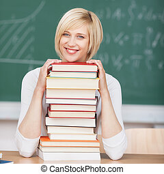 smiling woman in classroom on stacked books
