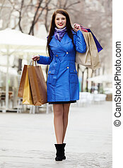 Smiling woman in  cloak with purchases
