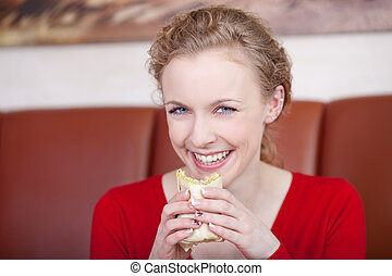 smiling woman in coffee shop eating wrap - smiling blond...