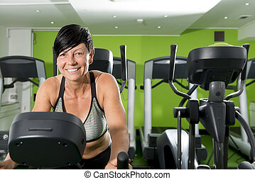 Smiling Woman in Crop Top on Elliptical Machine in Gym