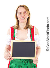 Smiling woman in dirndl holding clean blackboard