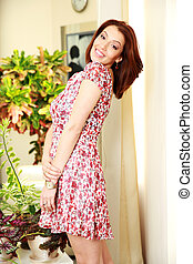 Smiling woman in dress standing at home