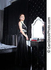 Smiling Woman in Elegant Black Dress at her Room