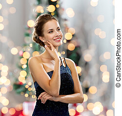 people, holidays, and glamour concept - smiling woman in evening dress showing earrings over christmas tree and lights background