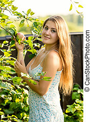 smiling woman in garden holding apple and looking at camera