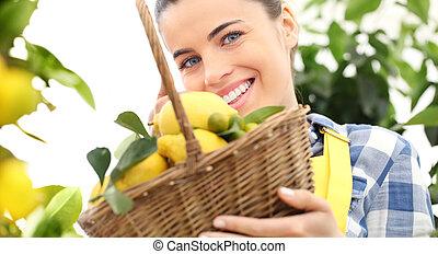 smiling woman in garden with basket wicker full of lemons