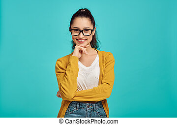 Smiling woman in glasses, blue background, positive emotion. Face expression, female person looking on camera in studio, emotional concept, feelings