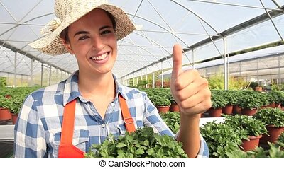 smiling woman in greenhouse with like hand