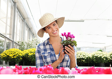 smiling woman, in greenhouse with cyclamen plants