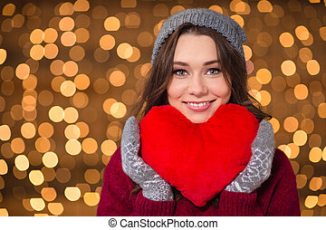 Smiling woman in grey hat and mittens holding red heart