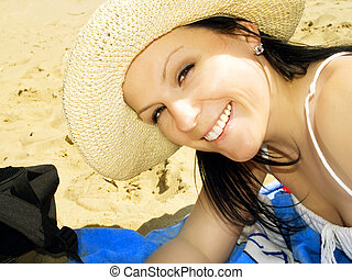 smiling woman in hat on the beach
