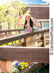 smiling woman in hat walking over the wooden bridge at sunny day
