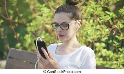Smiling woman in headphones with smartphone